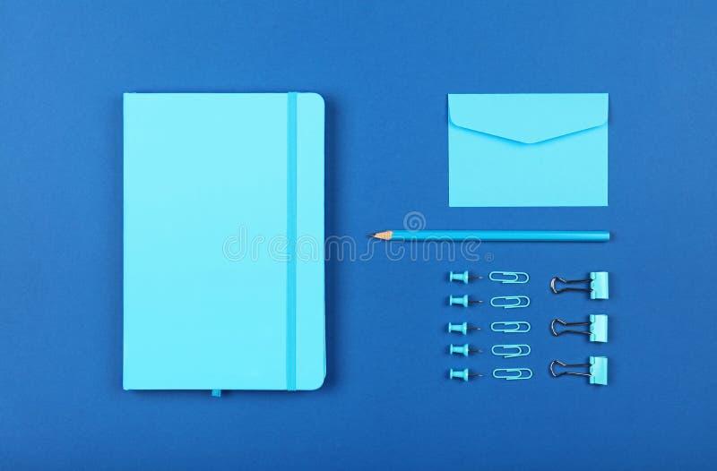 Legt de keurig georganiseerde kantoorbehoeftenvlakte van blauw stock foto's