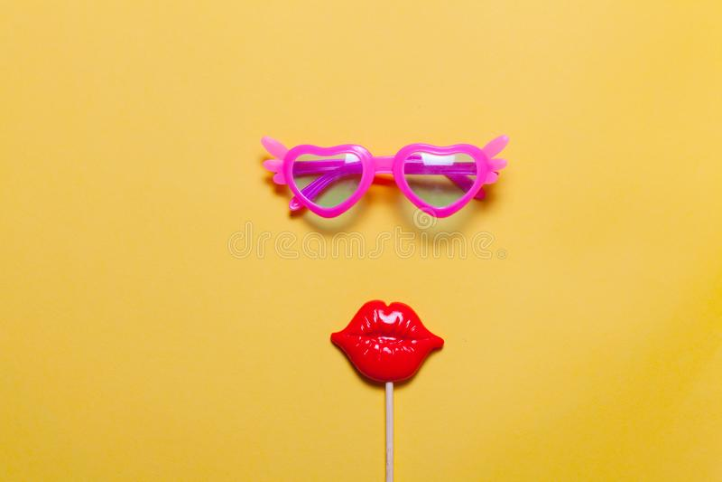 Legt de vakantie minimalistic vlakte: grappige roze zonnebril en maskerade plastic lippen op stok Gele achtergrond stock fotografie