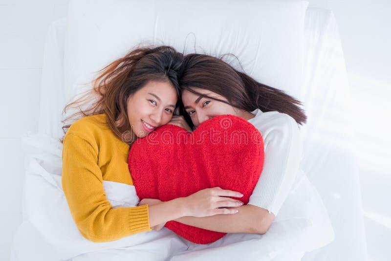 Legt het lesbische LGBT Paar van Azië op bed en koestert de vorm van het het hoofdkussenhart van de regenboogkleur samen met gelu royalty-vrije stock foto's