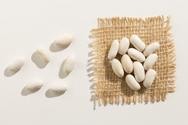 Legumbre de la haba de marina de guerra Ciérrese para arriba de granos extienden por la tabla blanca imagen de archivo libre de regalías