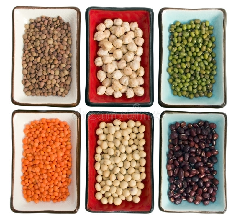 Legumes. Close up of six little dishes full of legumes (from left clockwise: small lentils, chickpeas, green beans, azuki beans, soy beans, red lentils). Focus royalty free stock photography