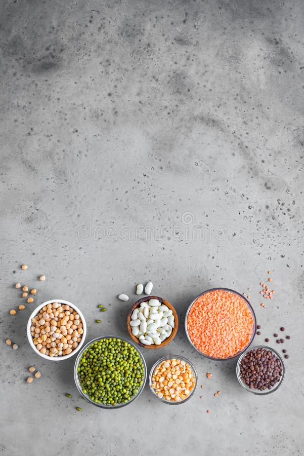 Legumes Assortment. Assortment of colorful legumes in bowls, lentils, kidney beans, chickpeas, mung, peas on grey background, top view, copy space. Healthy food royalty free stock photos