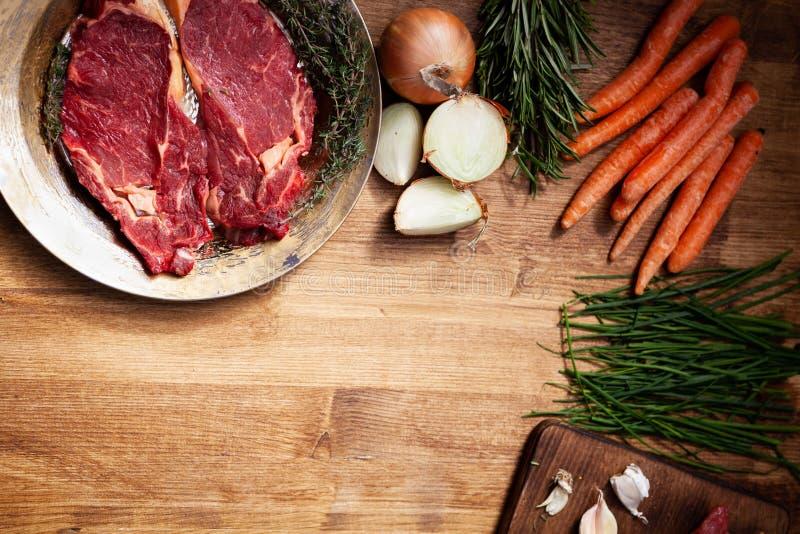 Legumes frescos ao lado da carne crua na placa dourada do vintage imagens de stock
