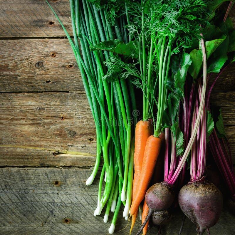 Legumes frescos - cenouras, beterrabas, cebola verde no fundo de madeira Conceito da colheita da dieta, cru fotos de stock royalty free