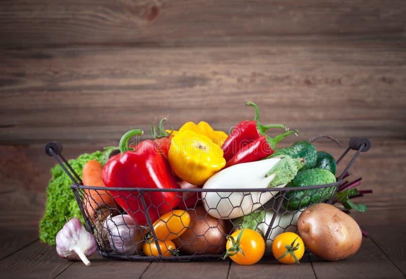 Legumes frescos na cesta na placa de madeira imagens de stock royalty free