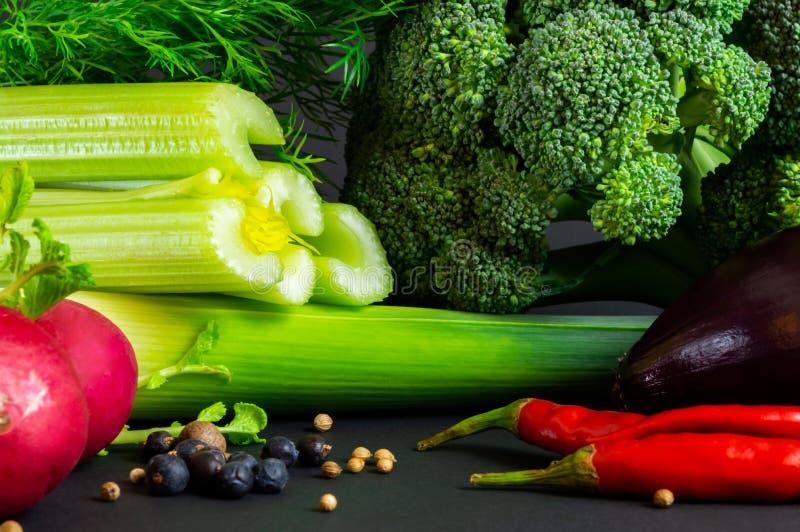 Legumes frescos no fundo preto: brócolis, aipo, alho poró, cebola vermelha, pimenta de pimentão, rabanetes, aneto Especiarias dif fotos de stock royalty free