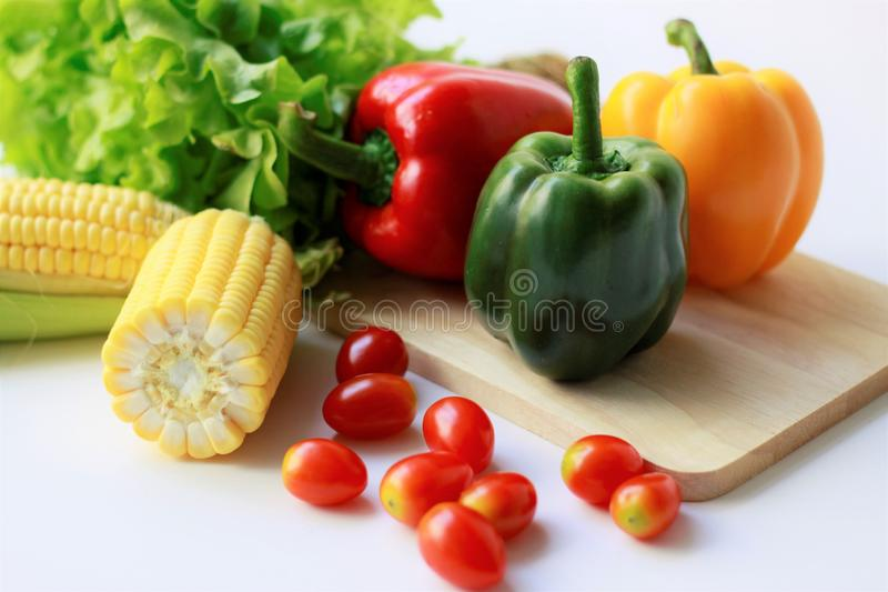 Legumes frescos nos grãos brancos do fundo, tomates, pimentas doces, salada verde fotografia de stock