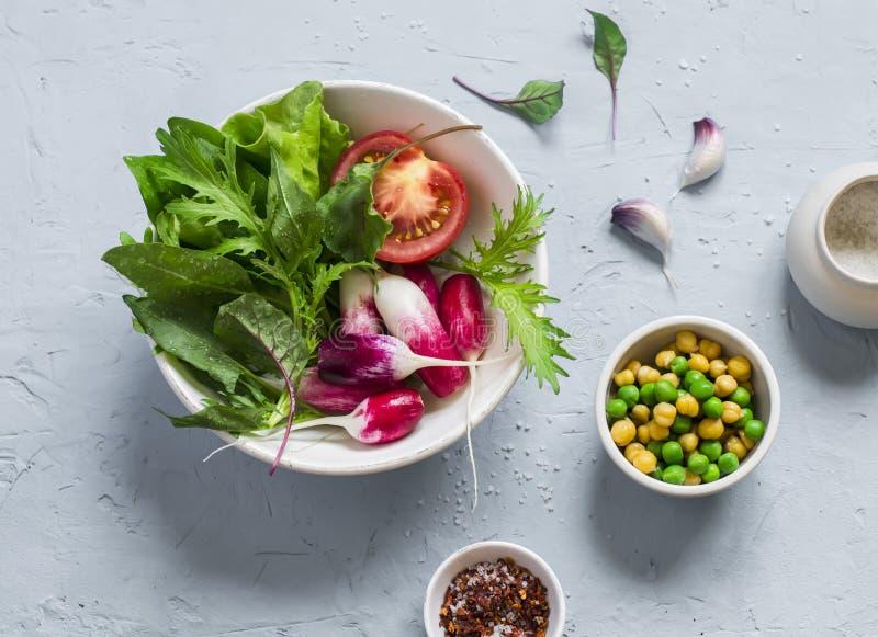 Legumes frescos - rabanetes, tomates, ervas do jardim e ervilhas verdes e grãos-de-bico em uma luz - fundo da pedra azul foto de stock