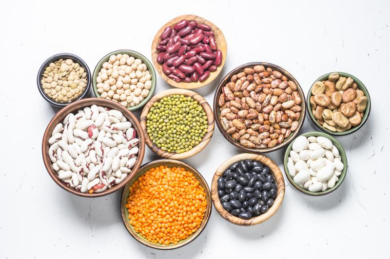 Legumes, lentils, chikpea and beans assortment on white. Legumes, lentils, chikpea and beans assortment in different bowls on white table top view royalty free stock photo