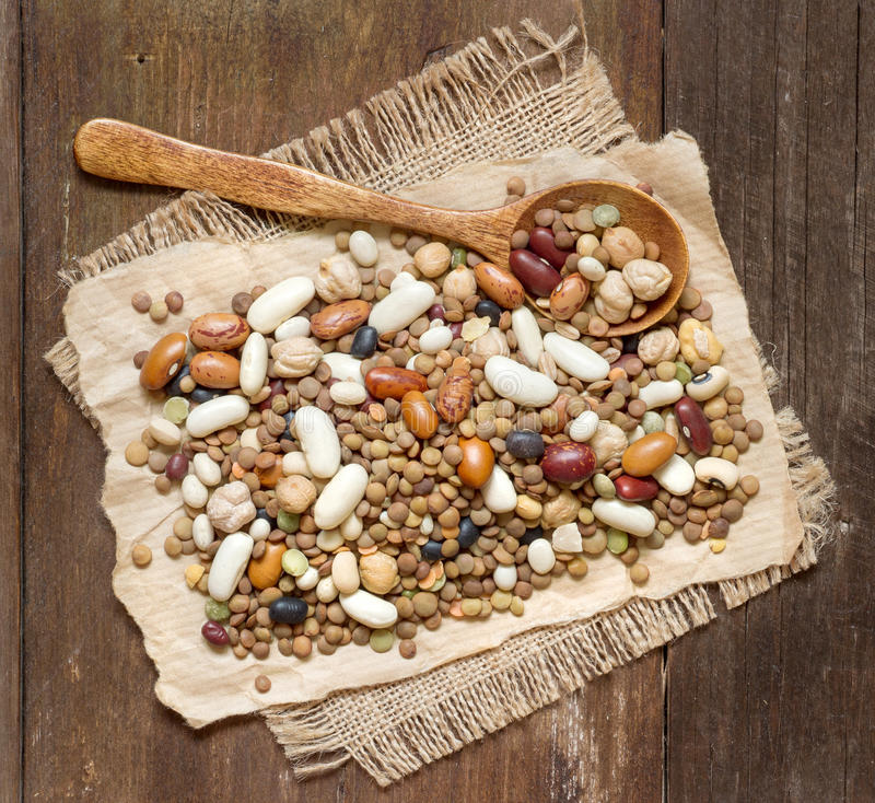Legumes mix. With a spoon on a wooden table royalty free stock photo