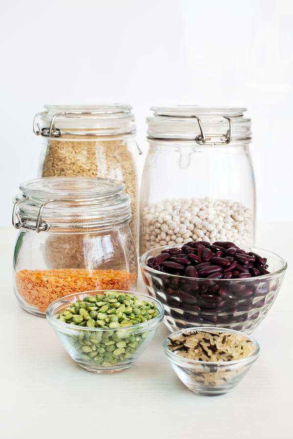 Legumes and rice. In glass jars: rice, french bean, lentil, kidney bean, green peas and wild rice stock photos
