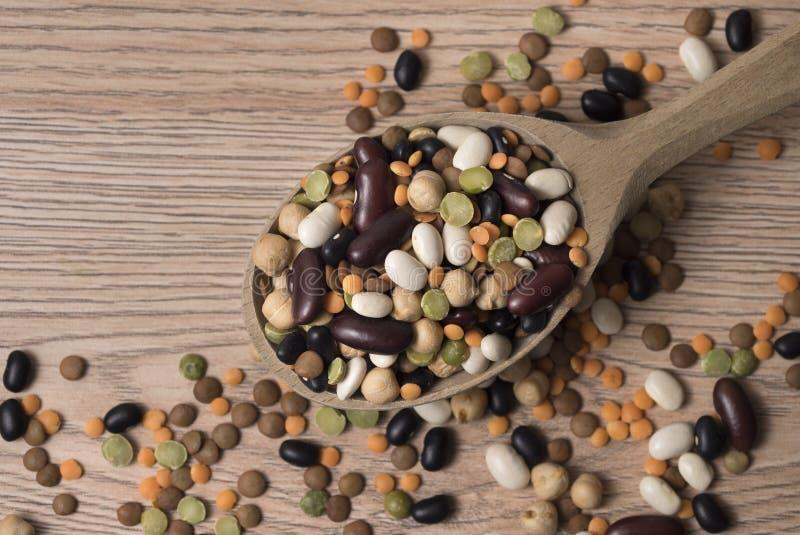 Legumi di vari generi in un cucchiaio di legno sulla tavola immagini stock