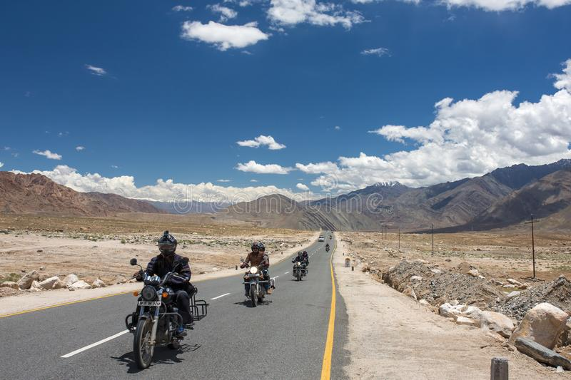 Group of motorbike tourists riding motorcycles on the Leh - Manali National highway in Ladakh, Northern India. Leh, India - July 1, 2017: Group of motorbike royalty free stock photos
