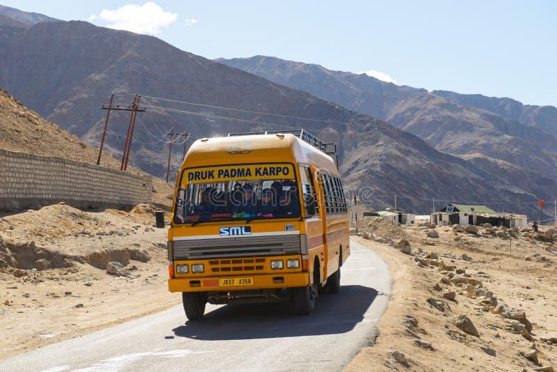 Leh India, Kwiecień, - 12, 2016: Autobusu szkolnego bieg przepustka droga na dużej wysokości Ladakh-Leh drodze w Himalajskiej gór zdjęcie stock