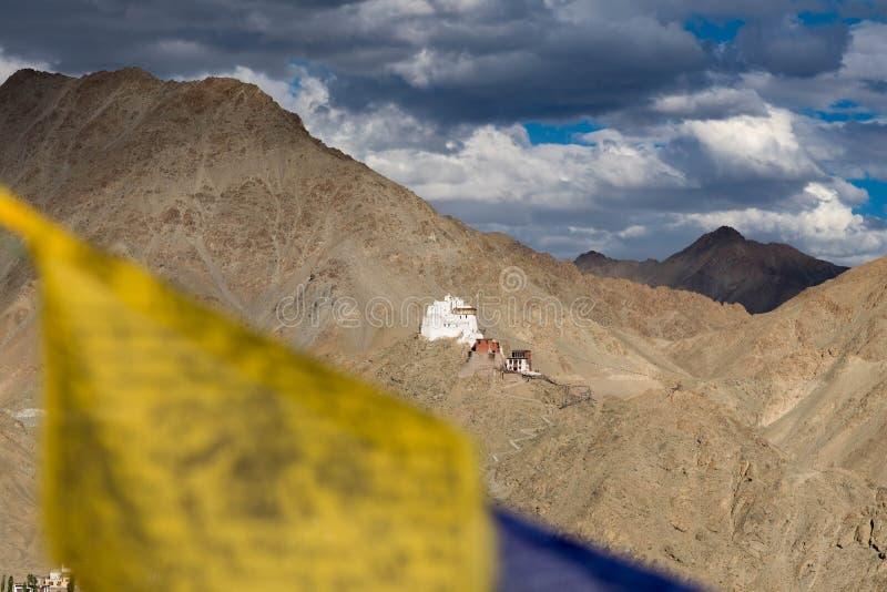 Leh slott i den Leh staden, Ladakh, Indien slotten är på bergvisningen från Santi Stupa med den suddiga Buddhaflaggan på foregrou royaltyfria bilder