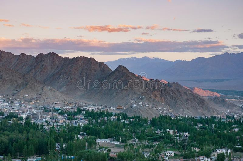 Leh town aerial cityscape -Ladakh mountains village, India. At sunset, sunrise clouds and green aspen trees royalty free stock photos