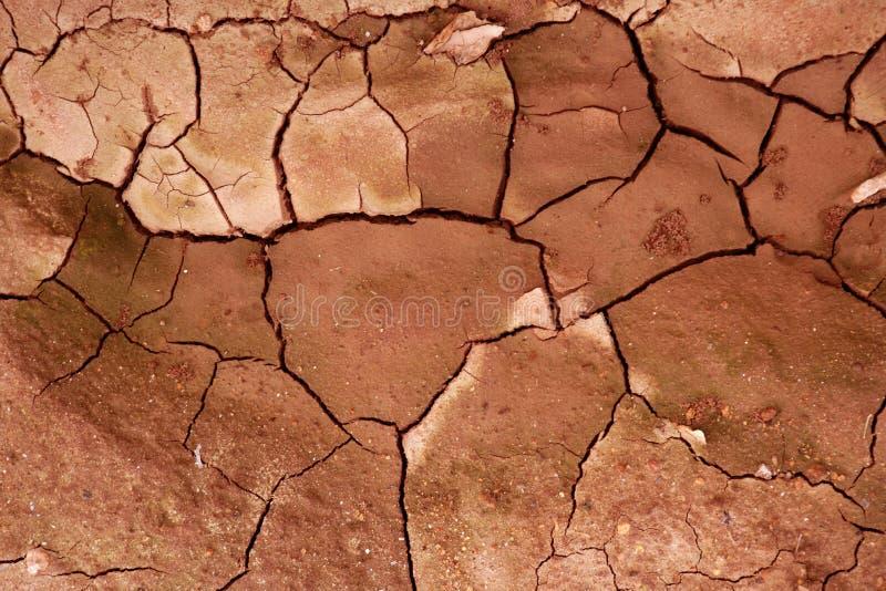 Lehm getrockneter gebrochener Beschaffenheitshintergrund des roten Bodens stockbilder