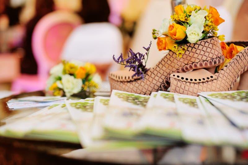 Lehm-Schuhe und Blumen auf einer Tabelle lizenzfreies stockbild