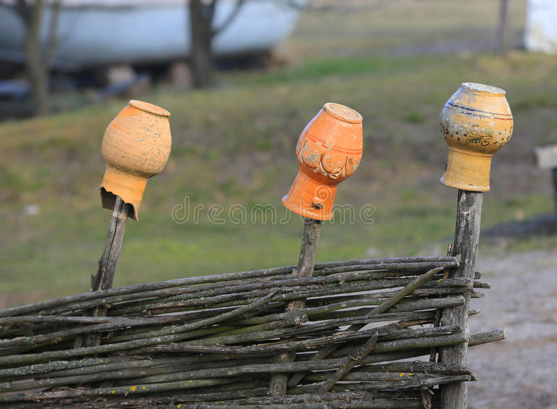 Lehmkrüge auf dem Zaun lizenzfreies stockbild