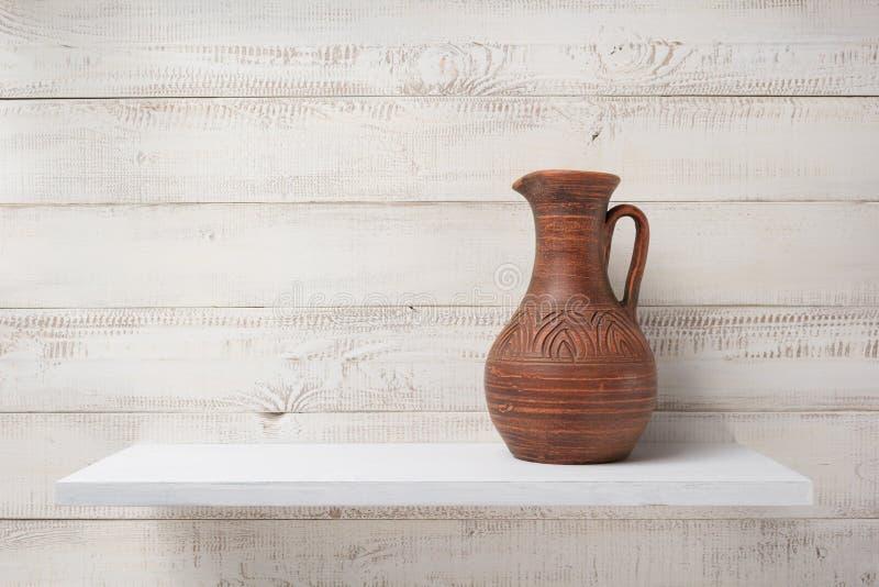 Lehmkrug am Regal auf weißem hölzernem Hintergrund lizenzfreie stockfotografie