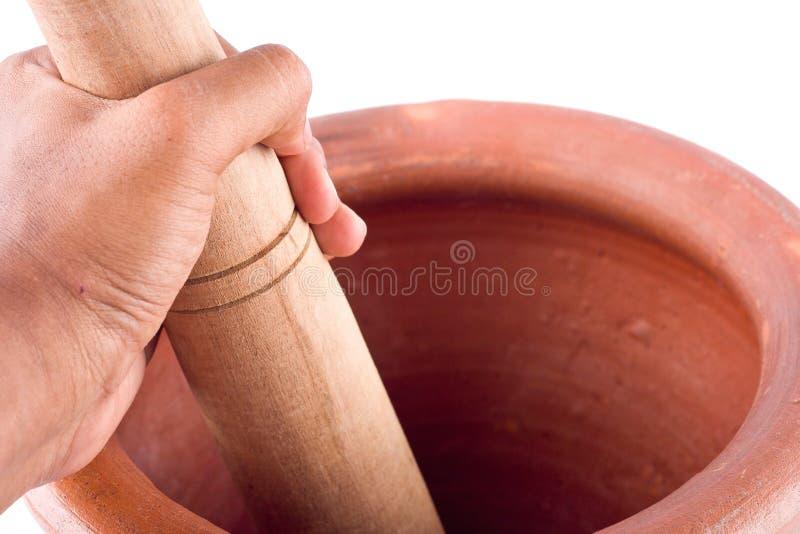 Lehmmörser und Holzstampfe wird benutzt, um den Bestandteil mit der männlichen Hand auf dem weißen Hintergrund zu mischen, der Kü lizenzfreie stockbilder