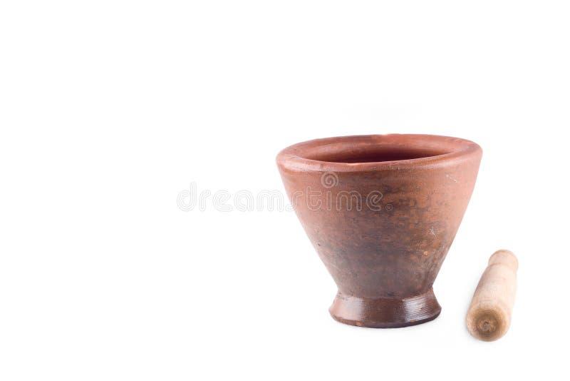 Lehmmörser und Holzstampfe wird benutzt, um die Bestandteile auf dem weißen Hintergrund zu mischen, der den lokalisierten Kücheng lizenzfreies stockfoto