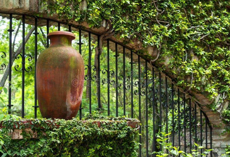 Lehmpitchertopf- und -metallstangen im mexikanischen kolonialgarten lizenzfreie stockbilder