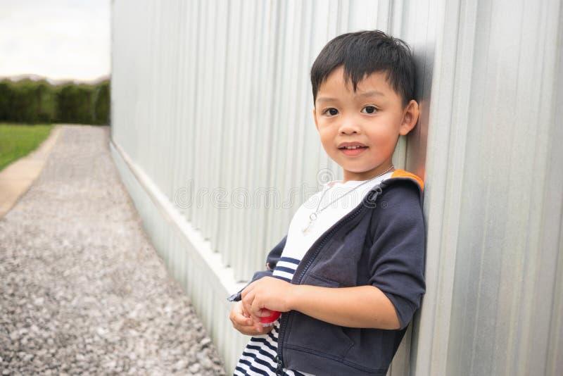 Lehnende Wand des glücklichen netten Jungen des Gebäudes und des Perspektivenweisenhintergrundes stockfotos