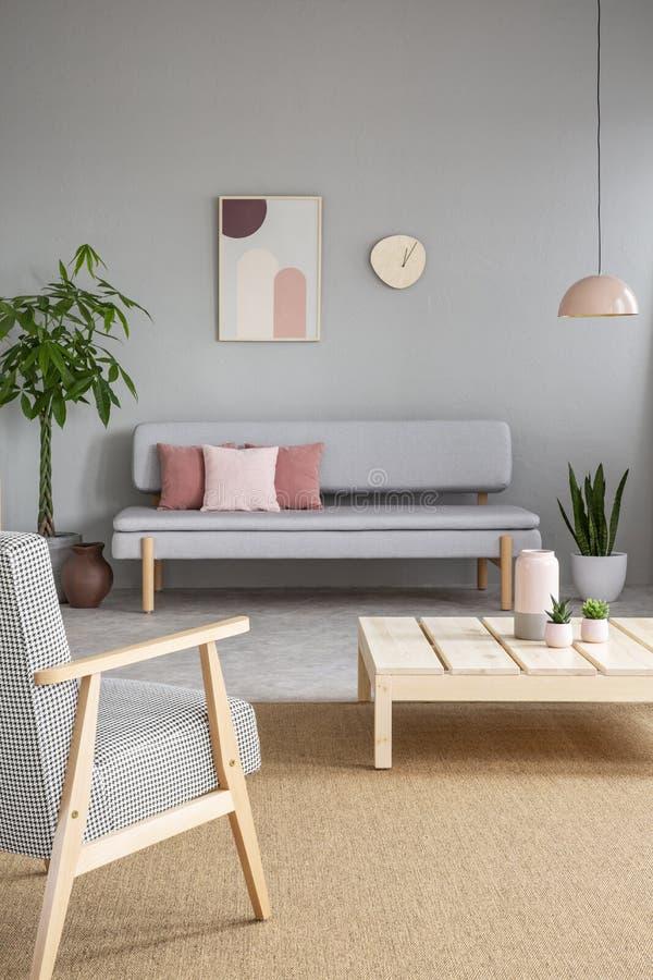 Lehnsessel und Holztisch im grauen Wohnzimmerinnenraum mit Beitrag lizenzfreies stockfoto
