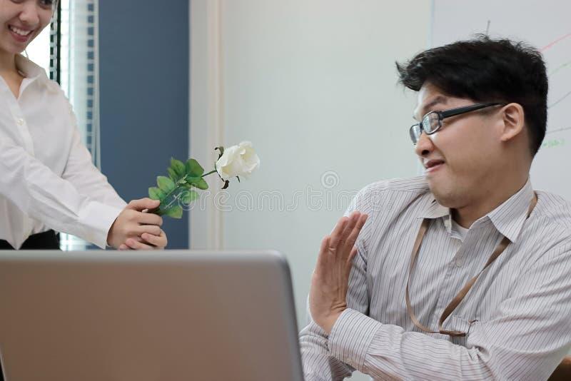 Lehnt verärgerter asiatischer Geschäftsmann der Weichzeichnung weiße Rosen von der attraktiven Frau ab Enttäuschtes Liebeskonzept stockfotografie
