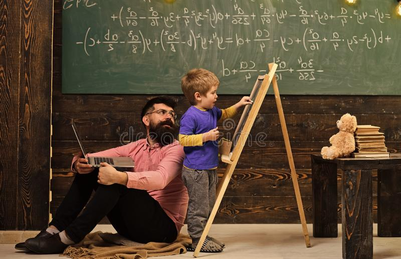 Lehrer überprüft Studentenschreiben auf Tafel Schüler, der mit seinem Tutor oder Vati beim Lösen der Aufgabe spricht Schöne fälli stockfoto