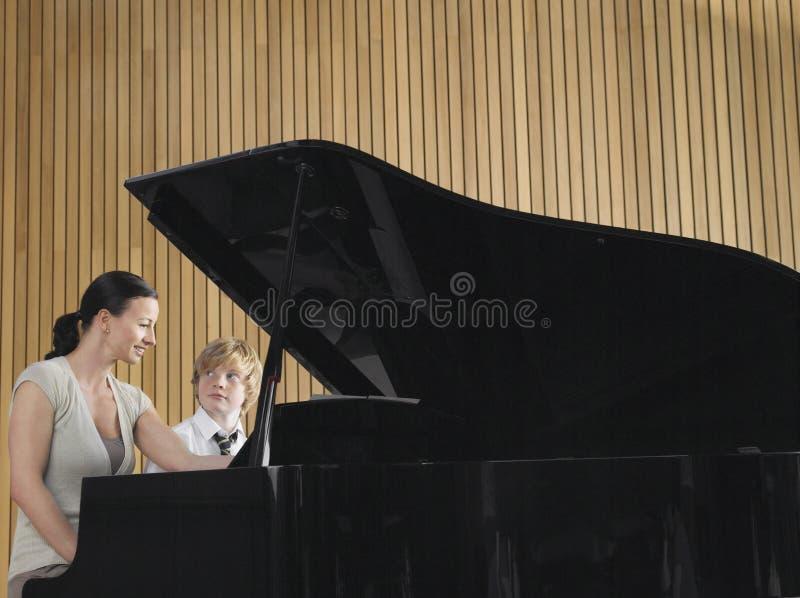 Lehrer-And Boy Playing-Klavier in der Musik-Klasse stockfoto