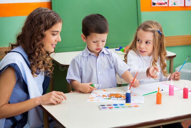 Lehrer With Children Painting am Schreibtisch stockfotos