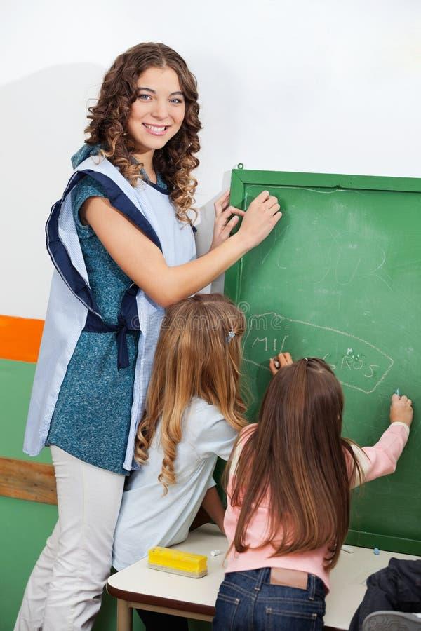 Lehrer And Children Writing auf Tafel lizenzfreie stockfotos