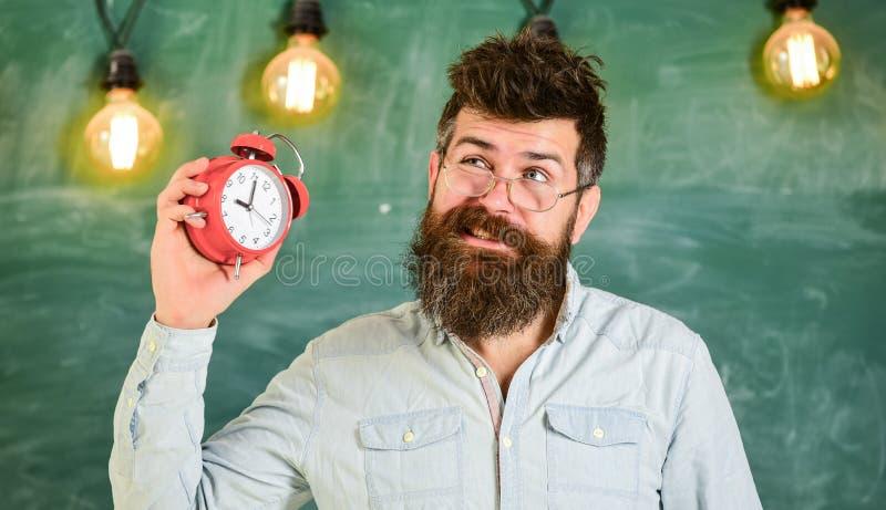 Lehrer in den Brillen hält Wecker Mann mit Bart und dem Schnurrbart auf gestörtem Gesicht hört Alarmglocke Schule Bell lizenzfreies stockbild