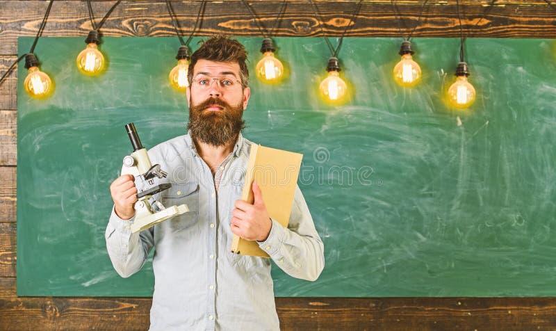 Lehrer in den Brillen h?lt Buch und Mikroskop Mann mit Bart und Schnurrbart auf ?berraschtem Gesicht im Klassenzimmer wissenschaf stockbilder