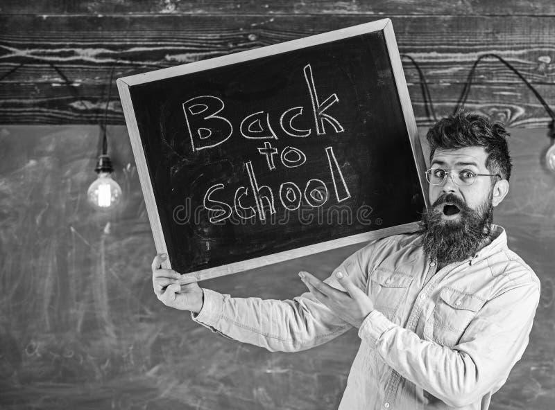 Lehrer in den Brillen h?lt Tafel mit Titel zur?ck zu Schule Mann mit Bart und Schnurrbart auf ?berraschten Gesichtswillkommen stockfotografie