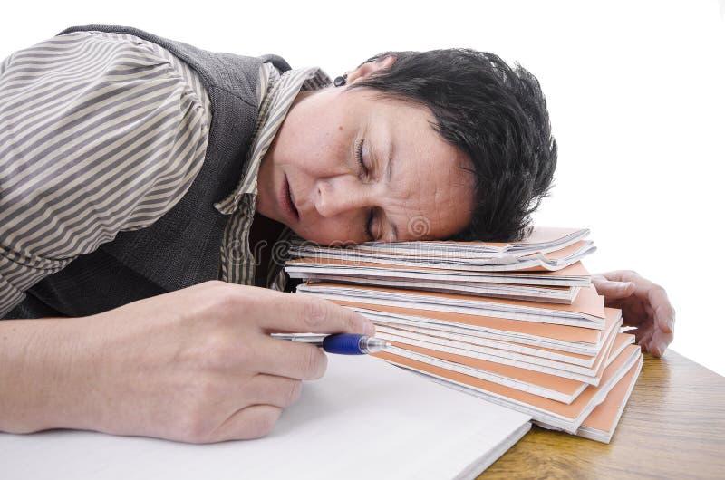 Lehrer, der auf einem Stapel von Büchern schläft lizenzfreie stockfotografie