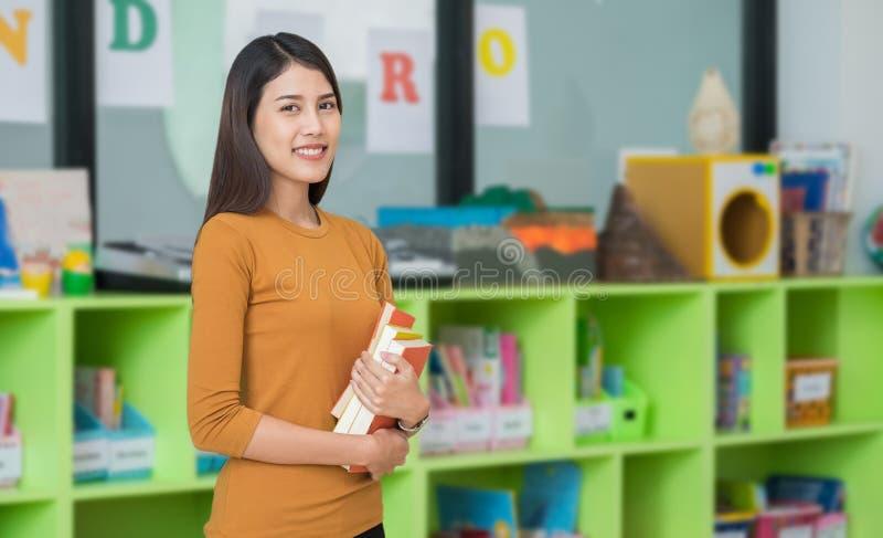 Lehrer, der das Lernen des Blickes an der Bibliothek in der Kindergartenvorschule h?lt getrennte alte B?cher stockbild