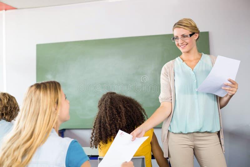Lehrer, der dem Studenten in der Klasse Papier übergibt lizenzfreies stockbild