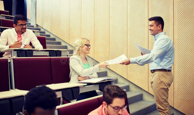 Lehrer, der den Studenten Tests am Vortrag gibt lizenzfreie stockfotos