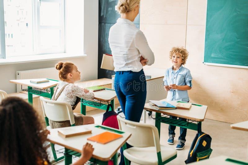Lehrer, der durch Klassenzimmer während der Lektion geht und mit spricht lizenzfreie stockbilder
