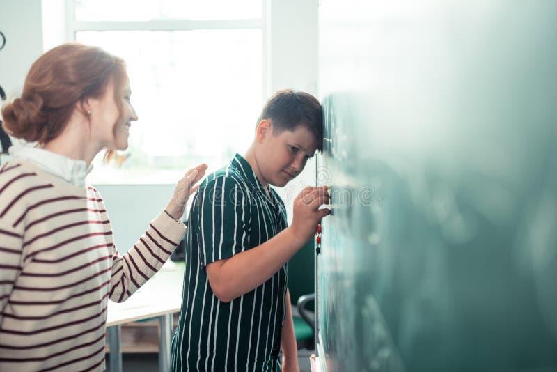 Lehrer, der herauf traurigen Schüler nahe der Tafel zujubelt lizenzfreie stockbilder