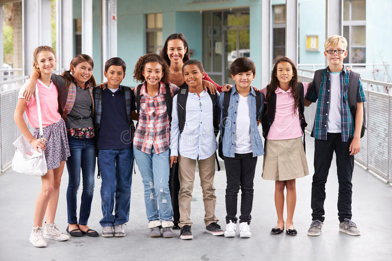 Lehrer, der heraus in der Schule mit Gruppe grundlegenden Kindern hängt stockbild
