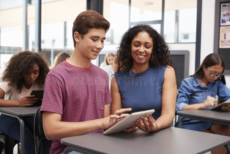 Lehrer, der Jugendschüler mit Tablet-Computer hilft stockfotografie