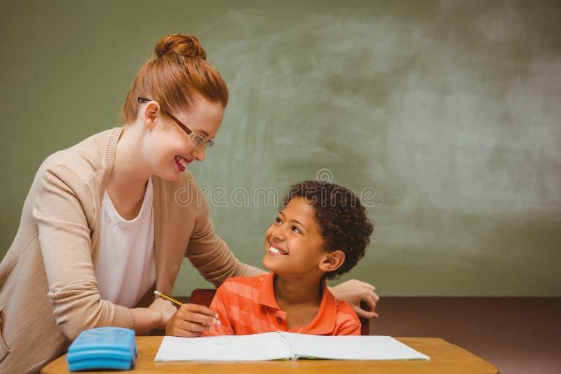 Lehrer, der kleinen Jungen mit Hausarbeit im Klassenzimmer unterstützt stockfotos