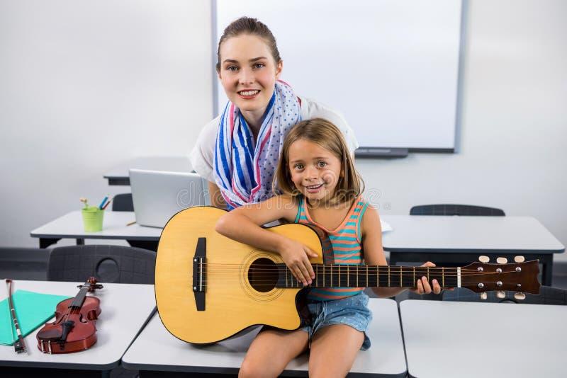 Lehrer, der Mädchen unterstützt, um Gitarre zu spielen lizenzfreie stockbilder