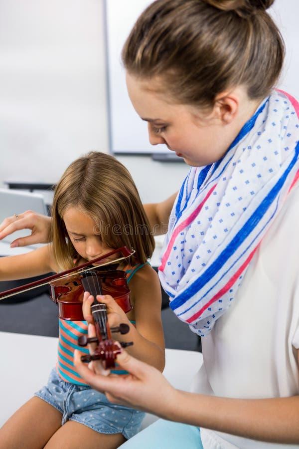 Lehrer, der Mädchen unterstützt, um Violine whiteboard im Klassenzimmer zu spielen lizenzfreie stockfotos