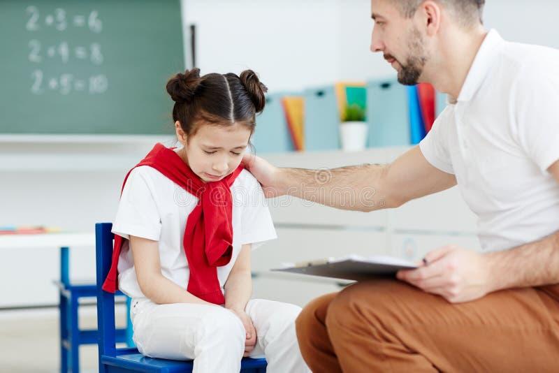Lehrer, der umgekipptes Schulmädchen tröstet lizenzfreies stockfoto