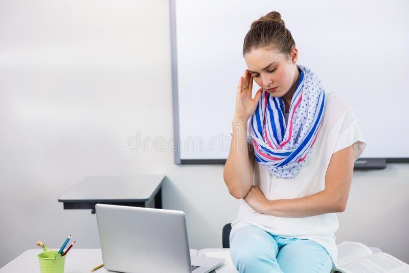 Lehrer, der unter Kopfschmerzen beim Sitzen im Klassenzimmer leidet lizenzfreies stockfoto